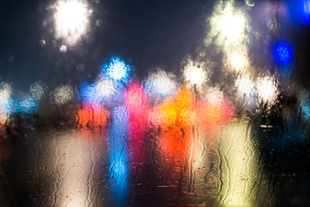 雨の日、夜市で車の窓から見る 写真素材