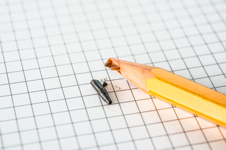 office physical pressure paper: Broken pencil lying on a notepad