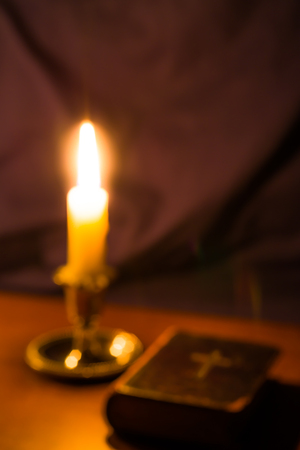 testaments: Old bible and candle on a wooden table. Image is out of focus