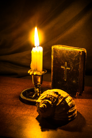 testaments: Old bible and candle with sea shell on a wooden table. Focus on the bible, image vignetting and in yellow toning