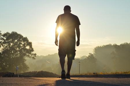man: Man walks off alone facing an unknown future.