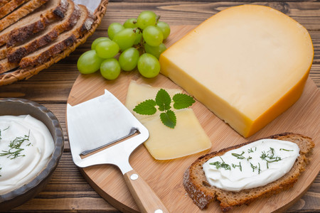 Cheese on board and woodem background