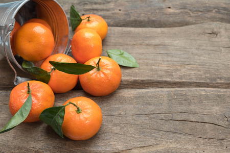 Fresh tangerines with leaf on wooden background