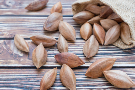 pili: Pili nuts in sack on wooden background