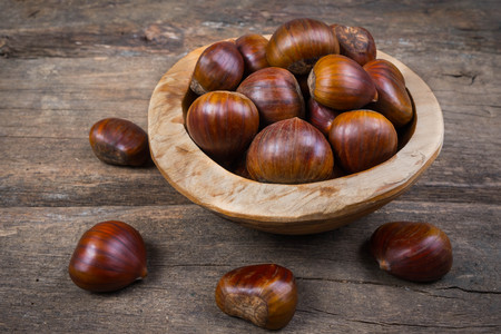 Fresh chestnuts in a bowl on wooden background
