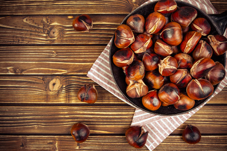 Chestnuts in a pan on wooden background