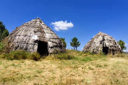Two traditional straw huts in greek country, on a sunny day Standard-Bild
