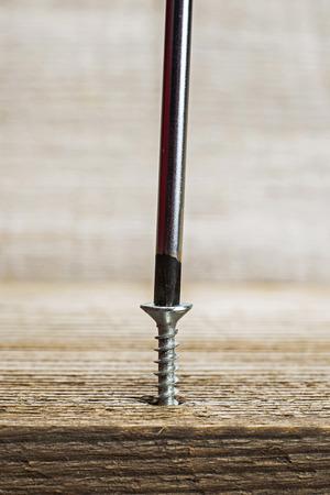 screwing: closeup of screwing screw into wooden plank