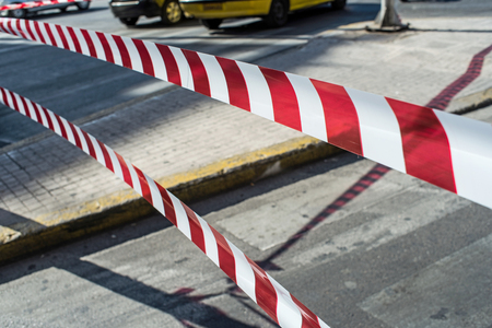 closed ribbon: Red and white striped security tape. police closing the traffic of the road. Stock Photo
