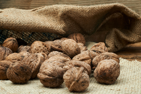burlap bag: Walnuts in a burlap bag on a wooden background.