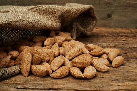 burlap bag: Almond nuts in a burlap bag on a wooden background. Stock Photo