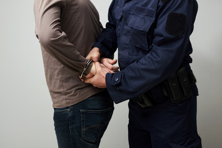 handcuffed: Closeup of a policeman handcuffing an illigal man.
