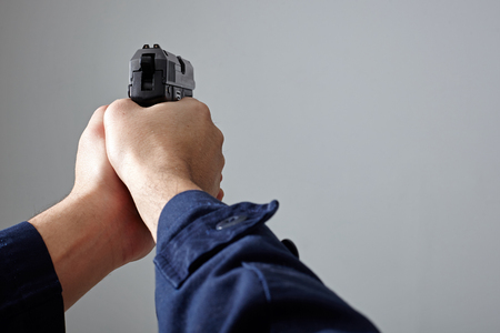 Closeup view of police officers hands aiming with gun.