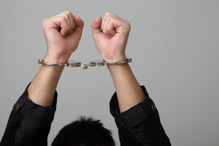 handcuffed: Closeup view of handcuffed man rising his hands. Stock Photo