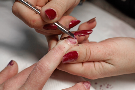 Manicurist removing the polish from the girl client nail at beauty salon. Stock Photo