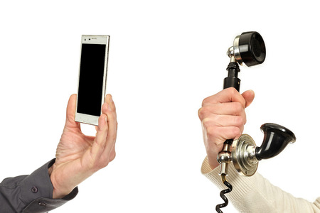 Man's hand holding a mobile phone and woman's hand holding a speaker of a vintage telephone.