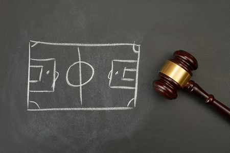 Judge gavel on blackboard background with painted soccer court. Imagens