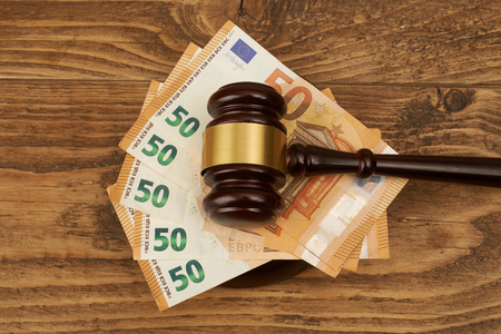Judge gavel and money stack on wooden table. Stock Photo