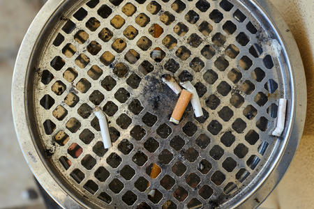 Closeup view of big ashtray with dropped cigarettes.
