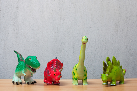 Four dinosaurs toys standing on a wooden floor.