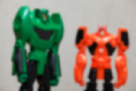 Blur image of green and orange robots on grey background.