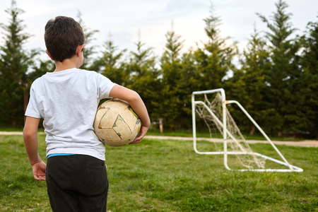 kid holding a soccer ball on garden field.