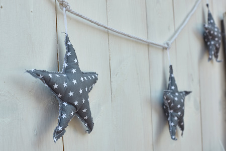 Three blue fabric stars on white wooden background.