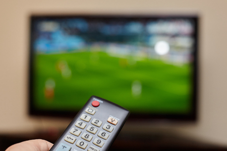 TV remote control and an open television as background.