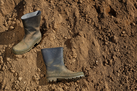 Worker boots on soil.