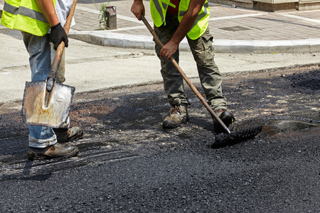 Workers using asphalt paver tools during road construction.
