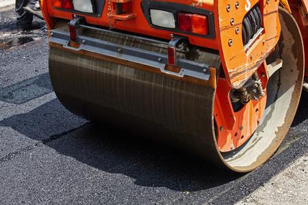 Roller machine working on the asphalt road construction. Stock fotó