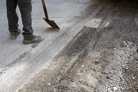Worker using asphalt paver tool during road construction.
