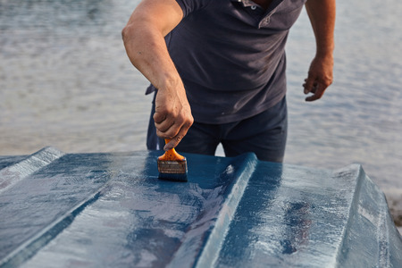 Man painting boat.Closeup view of hand holding a paintbrush with blue color.