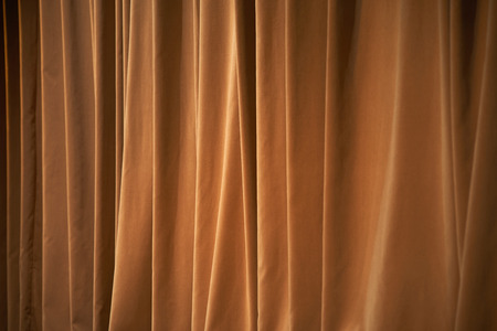 Brown curtains of a theater as background.