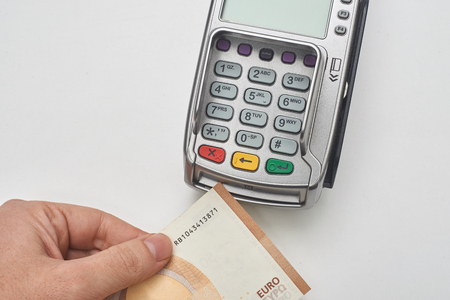 Businessman using payment terminal to pay with cash. Standard-Bild - 121627068
