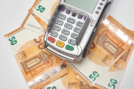 Credit card reader on money background.