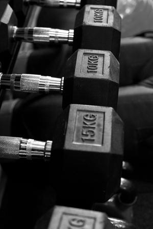 Metal dumbbells on rack in sport fitness center.Gym equipment.