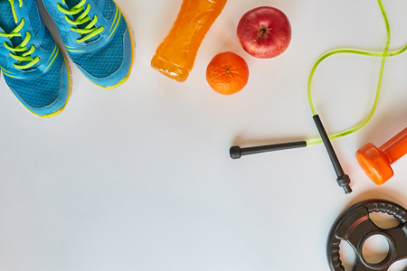Fitness concept.Fruits, gym equipment and sport clothing on white background.Healthy lifeslile.