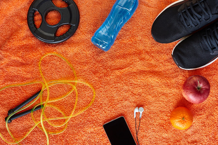 Fitness concept.Fruits, gym equipment and sport clothing on orange towel background.Healthy lifeslile. Stock fotó