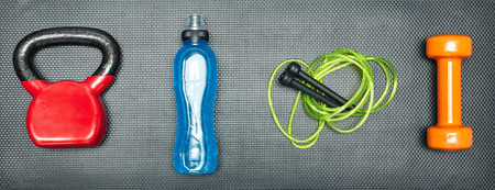 Gym concept. dumbbell, skipping rope,training weight and energy drink on step equipment background.Healthy lifeslile.Banner. Standard-Bild - 121627102