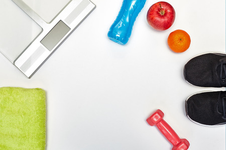 Fitness concept.Fruits, scale, gym equipment and sport clothing on white background.Healthy lifeslile. Banque d'images - 121627104
