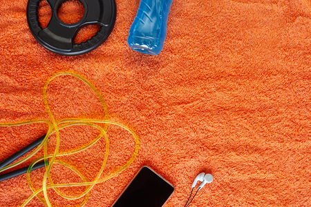 Fitness concept.Fruits, gym equipment and sport clothing on orange towel background.Healthy lifeslile. Standard-Bild - 121627105