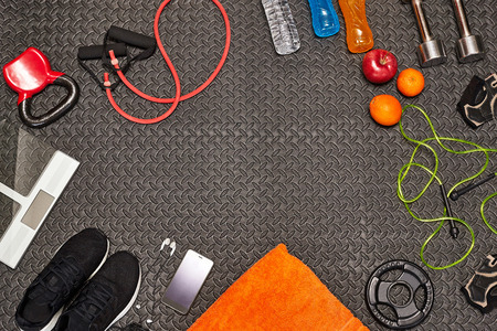Fitness concept.Fruits, gym equipment,water, energy drinks and sport clothing on gray background.Healthy lifeslile.