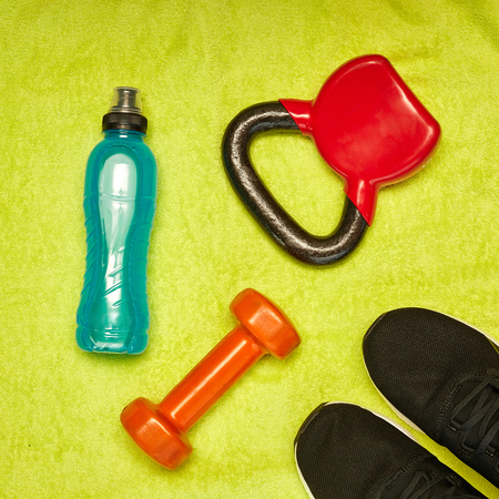 Fitness concept.Gym equipment and sport clothing on green towel background.Healthy lifeslile. Standard-Bild - 121627113