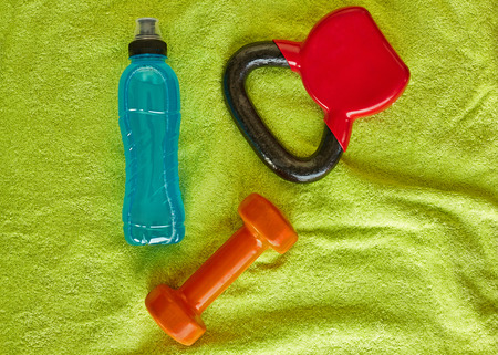 Fitness concept.Gym equipment and sport clothing on green towel background.Healthy lifeslile.