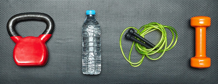Gym concept. dumbbell, skipping rope,training weight and energy drink on step equipment background.Healthy lifeslile.Banner. Standard-Bild - 121627118