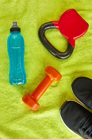 Fitness concept.Gym equipment and sport clothing on green towel background.Healthy lifeslile. Stock fotó - 121627139