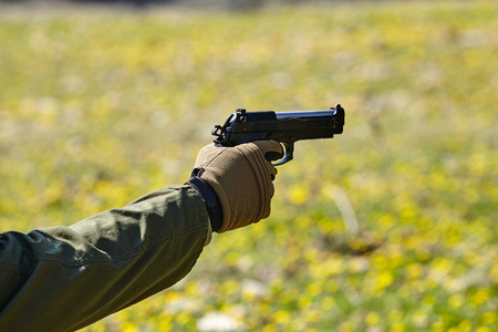 Soldiers hand points with a gun. Military concept. Stock fotó