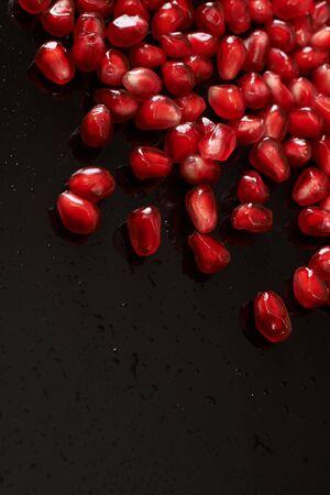 pomegranate seeds on black background.