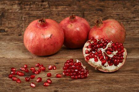 ripe pomegranate fruits on wooden table. Reklamní fotografie